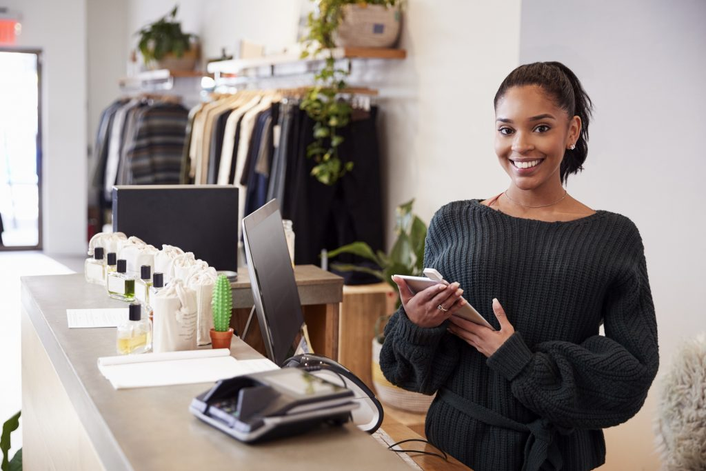 Female assistant smiling from the counter in retail store